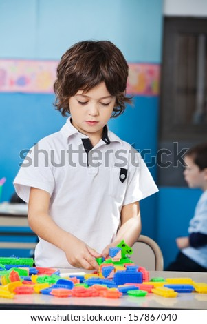 Little boy playing with colorful construction blocks in classroom - stock photo