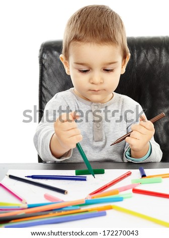 Little boy playing with colorful pencils, trying to draw
