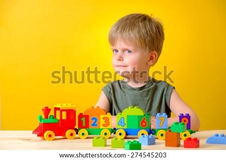 Little boy playing with colorful plastic blocks with numbers.