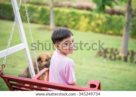 Little boy playing with dog in the  park - stock photo