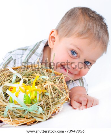 Little boy playing with easter eggs in basket