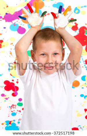 Little boy playing with flowers, the boy shows his hands painted