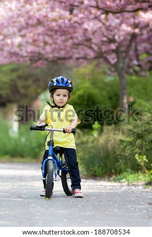 Little boy playing with his bike outdoors in the park - stock photo