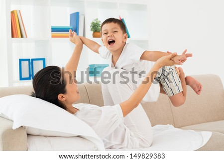 Little boy playing with his mother at home