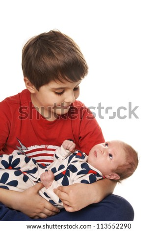 Little boy playing with his new newborn baby sister isolated on white background - stock photo