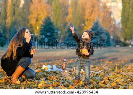 Little boy playing with his sister in the park in autumn. Girl blowing soap bubbles and little brother catches them. Cheerful, happy kids playing in the park in autumn. - stock photo