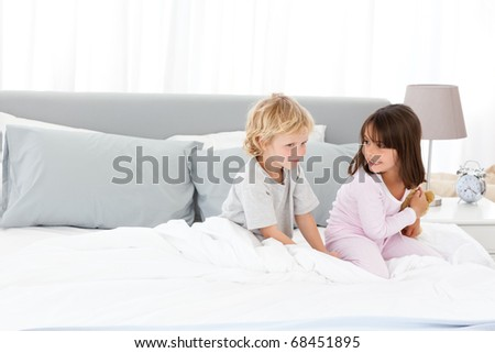 Little boy playing with his sister on their parents' bed in the morning