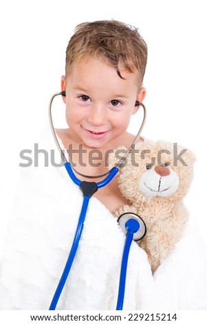 little boy playing with his teddy bear doctor - stock photo
