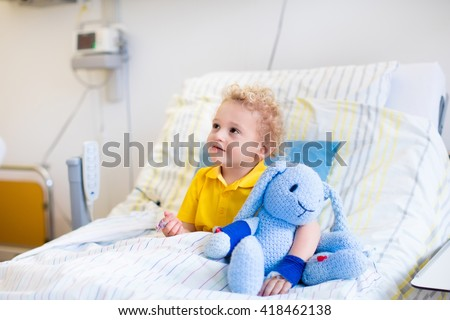 Little boy playing with his toy in bed in hospital room. Child with IV tube and pulse oximeter in modern clinic. Kid recovering from sickness. Post operative care at children station. Kids health care - stock photo
