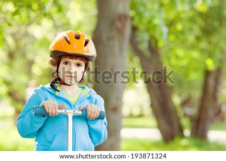 Little boy playing with kick scooter outdoors dressed in a colourful safety helmet and fleece jacket  - stock photo