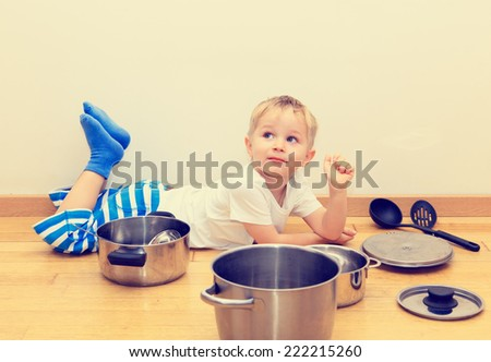little boy playing with kitchen utensils at home - stock photo