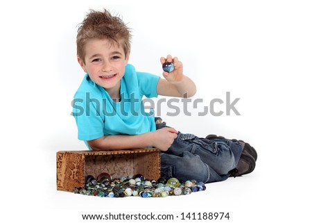 Little boy playing with marbles - stock photo