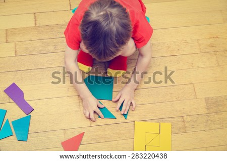 little boy playing with puzzle, early education concept - stock photo