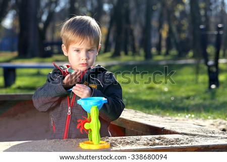 little boy playing with sand in a playground - stock photo