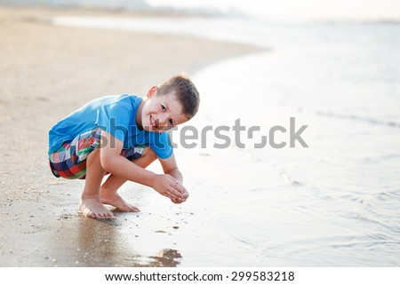 Little boy playing with sand on coastline - stock photo