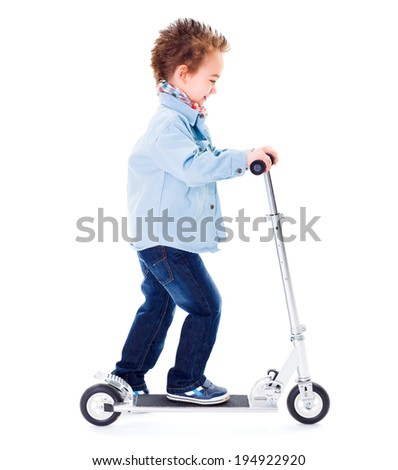 Little boy playing with scooter on white background - stock photo