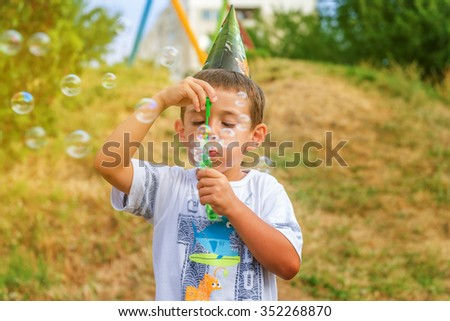 little boy playing with soap bubbles in summer