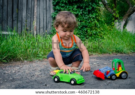 Little boy playing with toy cars in the yard in the summer.