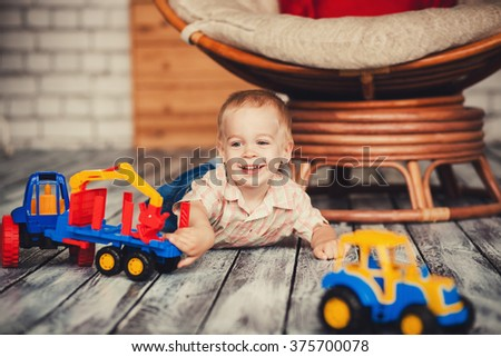 little boy playing with toys on the floor. happy childhood - stock photo