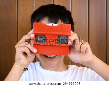 little boy playing with vintage 3d viewer - stock photo