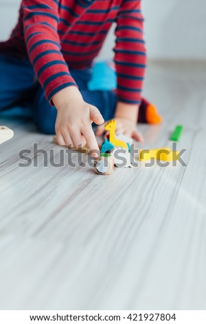 Little boy playing with wooden colorful toys. Copy space on the floor.