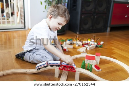 Little boy playing with wooden train set - stock photo