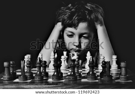 Little boy plays chess. BW