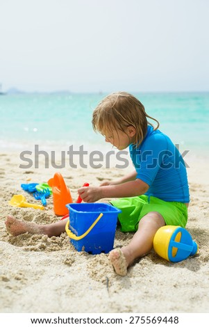 Little boy plays in the sand at the beach