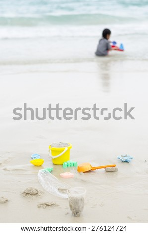 Little boy plays in the sand at the beach - stock photo