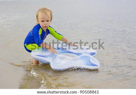 Little boy plays near the water