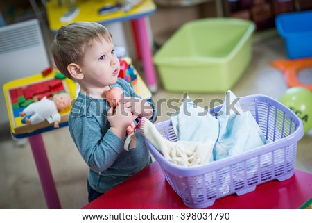 Little boy plays with a doll