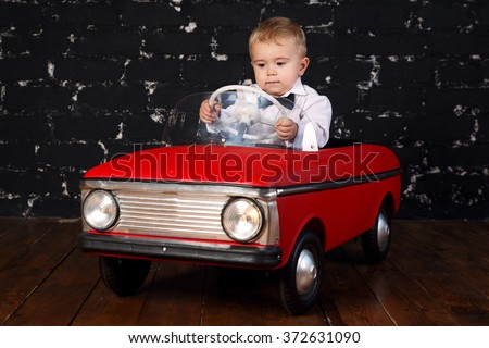 Little boy plays with big red toy car, black background - stock photo