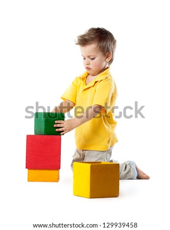 little boy plays with cubes, isolated on white - stock photo