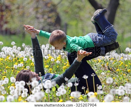Little boy plays with his mother in nature - stock photo