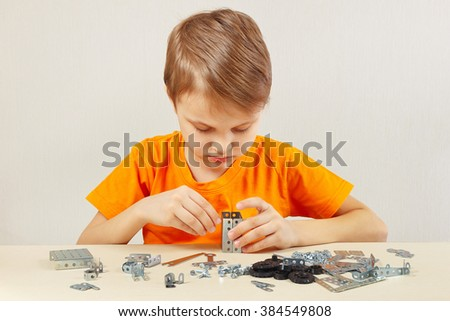 Little boy plays with mechanical constructor at the table - stock photo