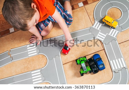 little boy plays with toy car