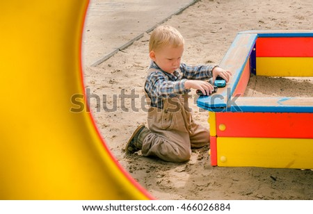 little boy plays with toy car in sand box in playground. Little child playing with car toy in summer garden.