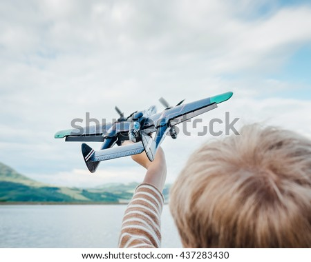 Little boy plays with toy military plane - stock photo