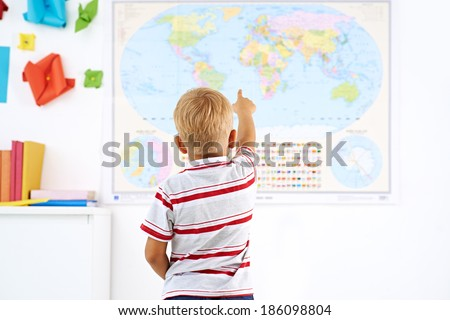 Little boy pointing at a map hanging on classroom wall - stock photo