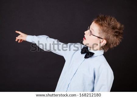 Little boy pointing out with a finger over the black