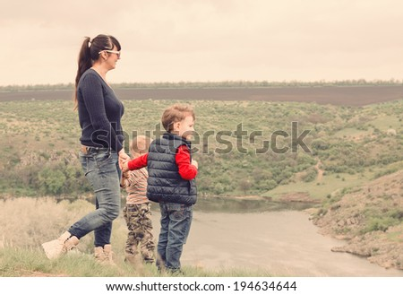 Little boy pointing to something in the countryside showing his mother a point of interest as they stand together on top of a grassy hill overlooking a steep valley and river - stock photo