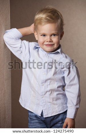 Little Boy portrait in shirt standing at the wall - stock photo