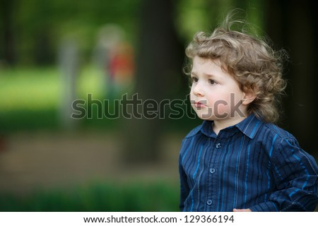 little boy portrait on summer playground - stock photo