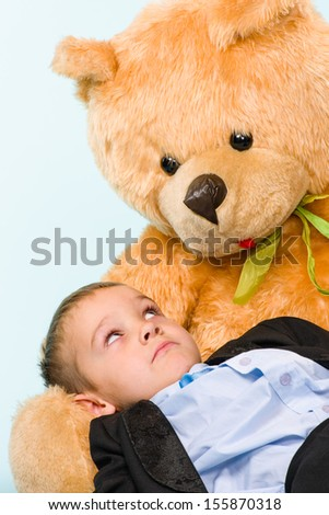 Little boy posing and playing with a teddy bear on studio, light blue background