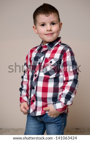Little boy posing in plaid shirt - stock photo