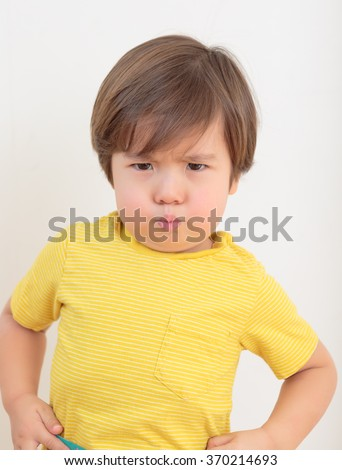 Little boy pouting. Toddler tantrum with an attitude. Grumpy preschooler wearing a yellow shirt. Two year old child on plain background, hands on hips, ready to argue and fight. Terrible twos.
