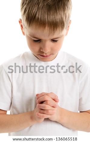Little boy praying - closeup isolated on white background - stock photo