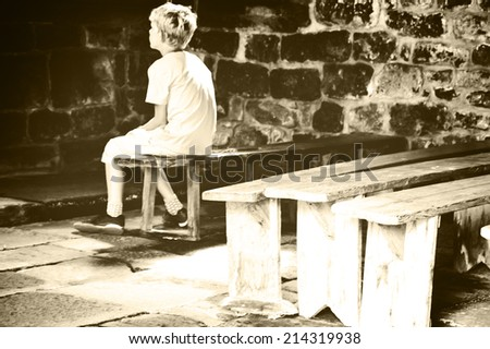 Little boy praying in old chapel. Retro aged photo. Sepia. - stock photo