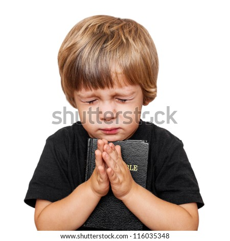 Little boy praying with the Bible in hand - stock photo