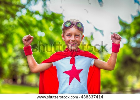 Little boy pretending to be superhero in park - stock photo